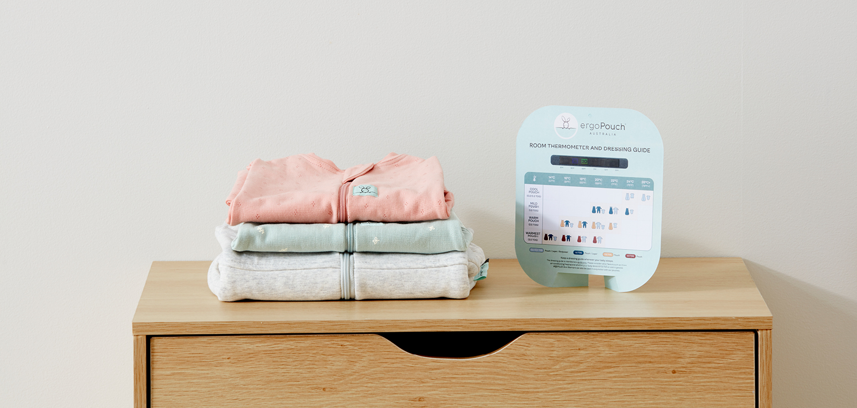 Image of products stacked on top of each other next to a ergoPouch Room Thermometer.