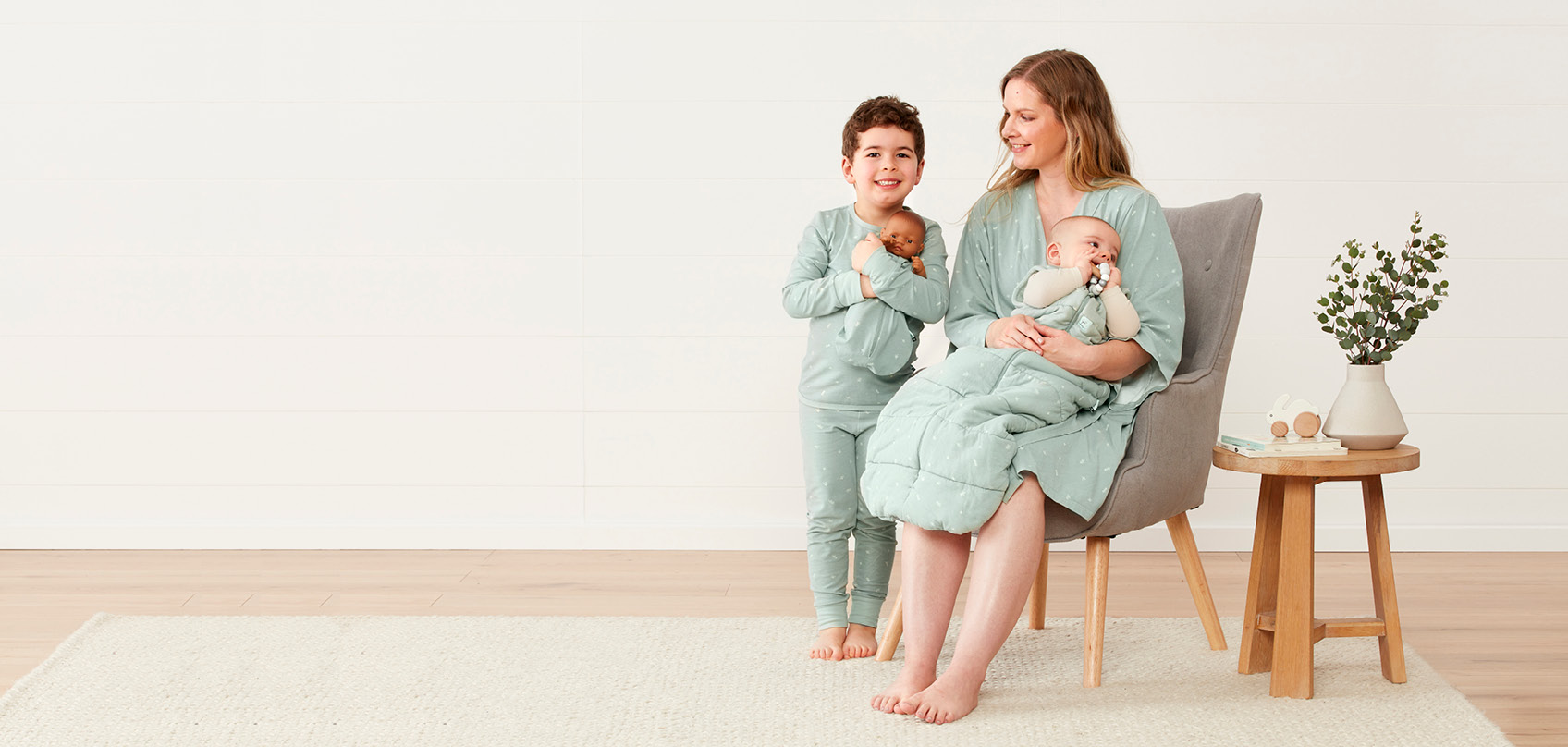 Image of family: Mum wearing Robe in Sage, Preschooler in Two-Piece Pjs in Sage and Infant in 2.5 TOG Jersey Bag in Sage.